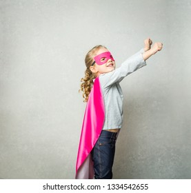 little girl standing against grey background in superhero outfit