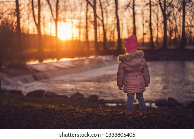 Little girl standing back by the river in sunset