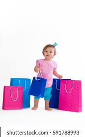 Little girl standing with colorful paper bags isolated on white background.