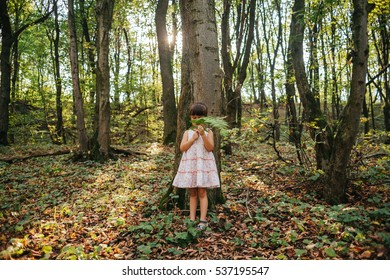 little girl standing in the forest with ferns