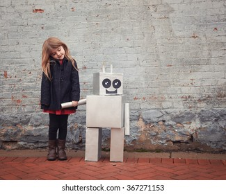 A little girl is standing with a metal cardboard robot against a brick wall outside for a friendship or inventor concept.