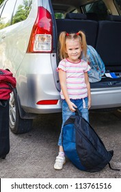 little girl standing near the car with backpacks