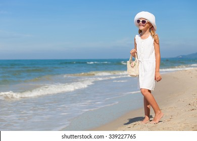 Little girl  standing on the beach at the day time
