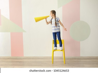 Little girl standing on chair and shouting into paper megaphone indoors