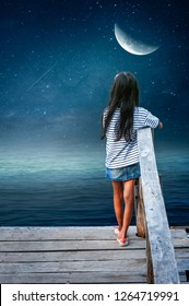 The little girl standing on the harbor bridge looked at the half moon in a lonely night.