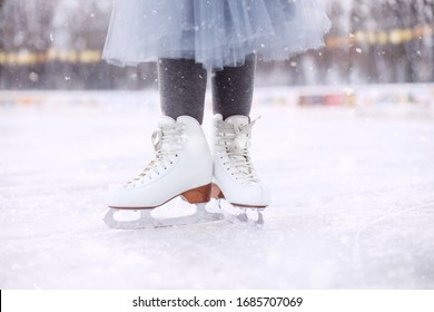 little girl is standing on ice in white figure skates.Winter active holiday concept.