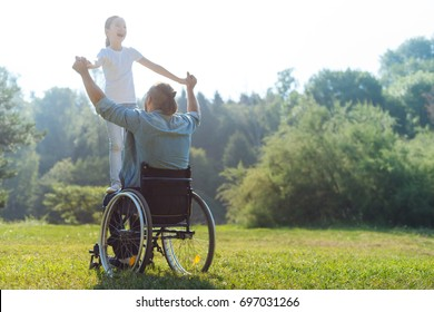 Little girl standing on lap of her father in wheelchair