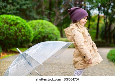 little girl standing on the track in the park after the rain and looking somewhere to the side
