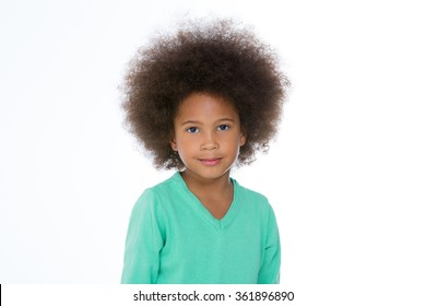 little girl standing on a white background and looking at the camera