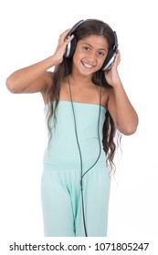 Little girl standing, putting the headphone and touching it on her head, isolated on a white background.
