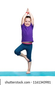 Little girl standing in tree yoga pose