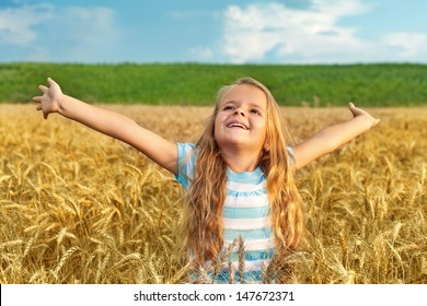 Little girl standing in wheat field with arms spread - late afternoon lights