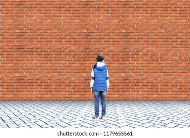 Little girl stands in embarrassment in front of a high brick wall