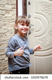 A little girl stands in the hallway of the apartment near the front door and smiles.