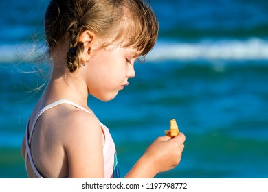 Little girl stands with her eyes down and holds one potato chip in her hand