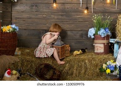Little girl stands with a lantern in a rustic interior