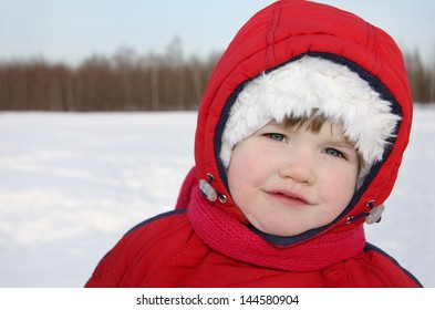 Little girl stands near forest at winter and looks into camera