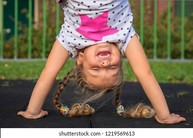 Little girl stands on her hands and smiles. Child has fun outside. Kid enjoys upside down. Exercises, coups, tumbling, standing upside down, laughter and happiness. Happy childhood concept.