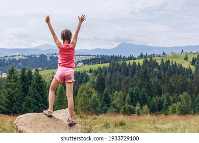 Little girl stands on a stone on a background of mountains. A child with raised hands stands back to the camera in nature