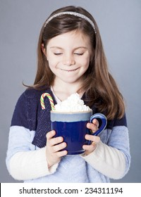 Little girl staring at a delicious cup of hot cocoa with candycane
