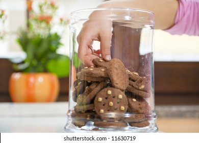 little girl stealing some cookies from the jar