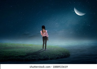 The little girl stood looking at the moon on a grassy island by the sea in a lonely beach.