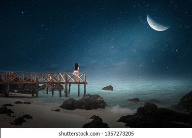 The little girl stood on the bridge looking at the lonely half moon night.