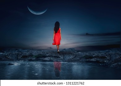 The little girl stood on a rocky island looking at the beautiful half moon.