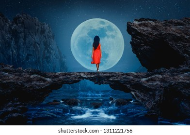 The little girl stood on a stone bridge looking at the full moon beautifully.