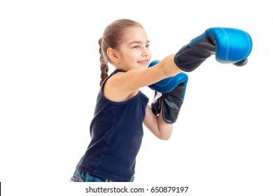 little girl stretches forward hand in large adult boxing gloves