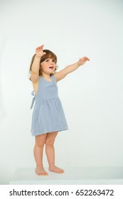 Little girl in a striped blue dress raised her hands and asks for help standing on a white cube on a clean white background