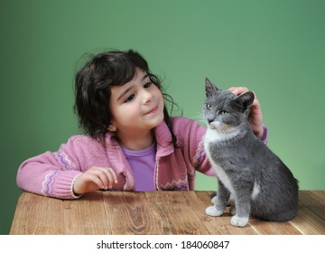 Little girl stroked the cat on the table
