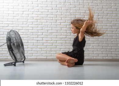 little girl struggling with heat and sitting in front of a fan with flying hair in an apartment on a bricky light wall background