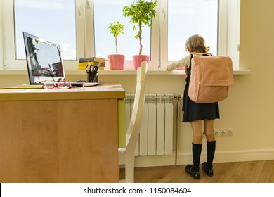 Little girl student with backpack in school uniform looks out the window, background is children's room, desk, computer. School, education, knowledge and children