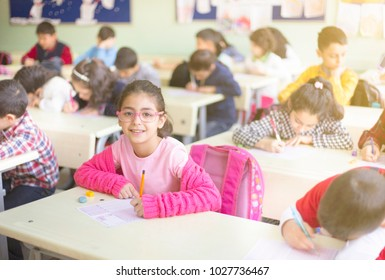 little girl student at the exam in the classroom