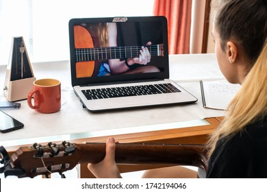 Little girl studying guitar lessons at home