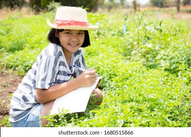 Little girl studying nature in the vegetables plot. She taking notes and studying via notebook to search for more information to make a growth report. Concept about natural conservation and nature stu