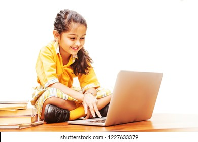 Little girl studying online using her laptop at home