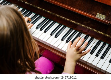 Little girl studying to play the piano at home