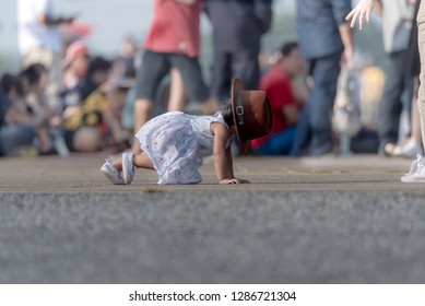 The little girl stumbling on rock because cannot see the way while walking and wearing big hat.
