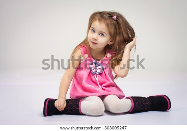 Little girl in stylish fun pink shirt and black boots, studio shot on a white background