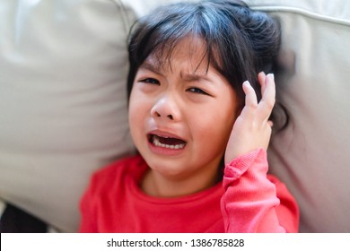Little girl suffering from headache and crying in sofa at home.Kid with attention deficit hyperactivity disorder (ADHD)
