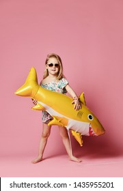 little girl in a summer dress, wears a balloon in the shape of a yellow shark-fish, celebrates a holiday, smiles broadly, against a pink background. The concept of children and recreation
