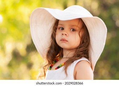 Little girl in summer hat in the park