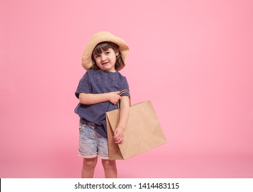 Little girl in summer hat with shopping bag , on isolated pink background, baby fashion concept