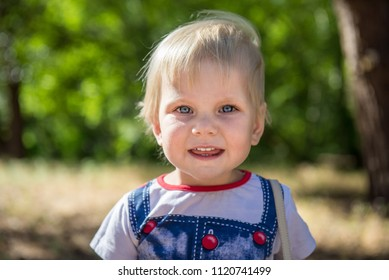 little girl in summer in the park. Portrait of a cute little girl in summer. Beautiful little blond girl on a walk in the park