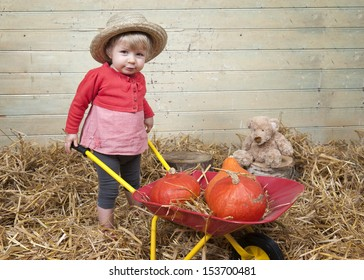 Little girl with summer straw hat in a barn with straw w