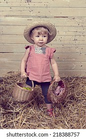 Little girl with summer straw hat in a barn with straw