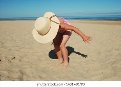The little girl in a sun hat near the sea on the summer beach.