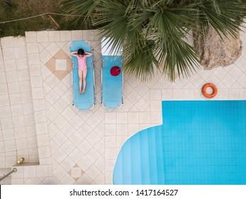 Little girl sunbathing by a swimming pool